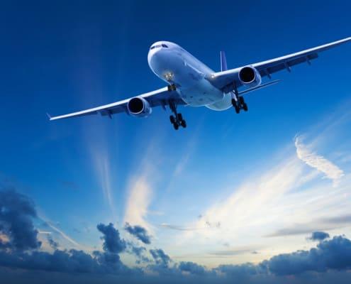 Evening flight: jet aircraft cruising in a blue sky after sunset